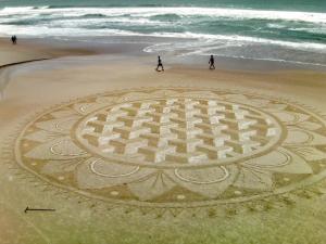 Desenho geométrico de grande proporção feito na areia da praia do Campeche.